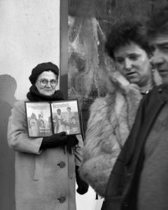An elderly lady stands holding an open copy of The Watchtower, a magazine published by The Jehovah's Witnesses, a Christian sect, on the pavement in Augsburg, Germany, as a heterosexual couple passes by.